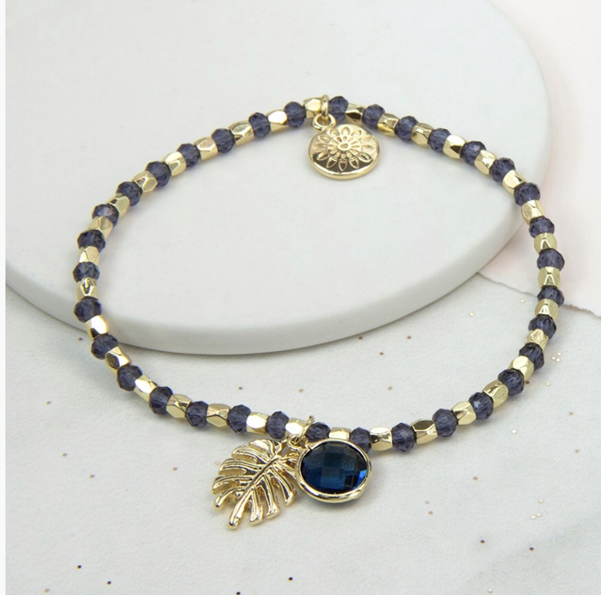 Gold and blue bead bracelet with palm leaf and Chrystal charm