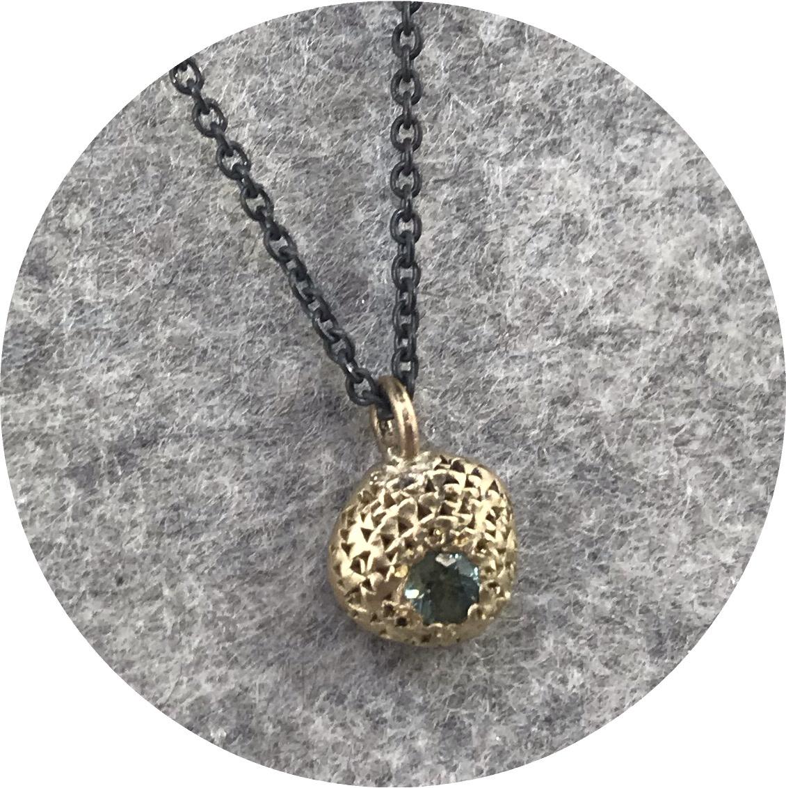Georgie Brooks- Textura Centra Pendant. 9ct yellow gold with 42cm black oxidised chain. 3mm green Australian Sapphire.