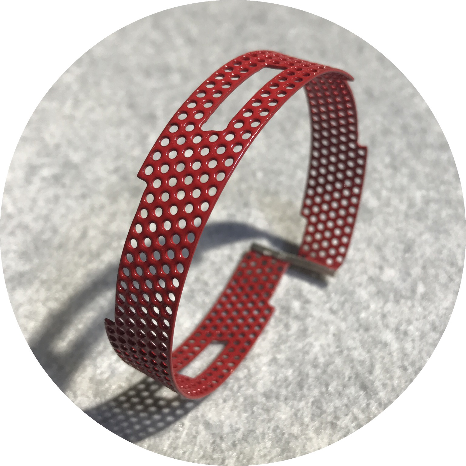 Jin Ah Jo- Perforation bangle, red powdercoated mild steel and sterling silver.