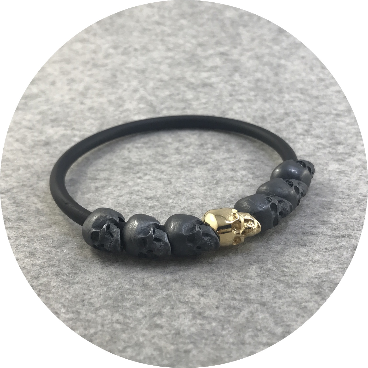 Fin Mahon - Seven Skull Bracelet in 9ct Yellow Gold, Oxidised Sterling Silver and Neoprene